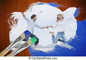 Composite image of couple jumping on the beach with...