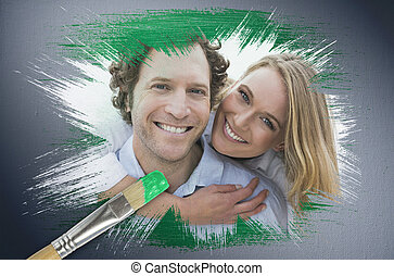 Composite image of couple smiling at camera with paintbrush...