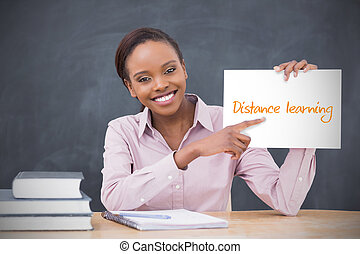 Happy teacher holding page showing distance learning in her...