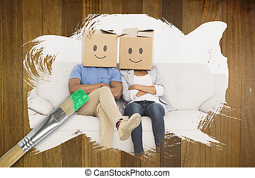 Composite image of couple wearing boxes on head