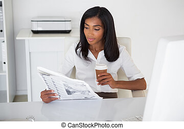 Pretty businesswoman reading newspaper at her desk in her...