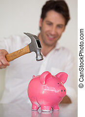 Casual businessman breaking piggy bank with hammer in his...