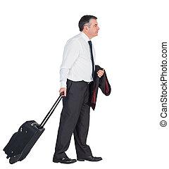 Mature businessman pulling his suitcase