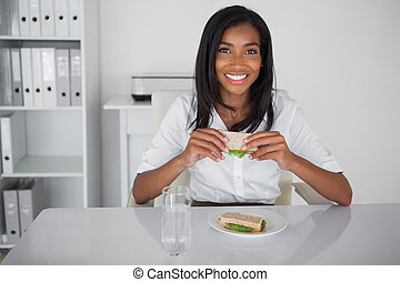 Happy businesswoman eating a sandwich at her desk