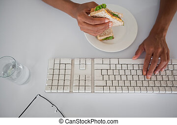 Businesswoman eating a sandwich at her desk