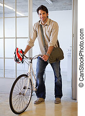 Casual businessman pushing his bike smiling at camera in the...