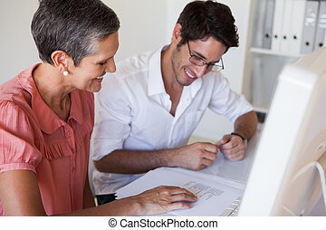 Casual business team working together at desk using computer...