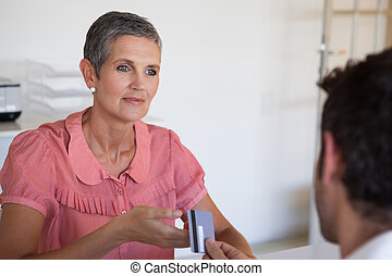 Casual saleswoman taking credit card from customer