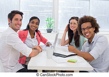Business people having a meeting together smile at camera