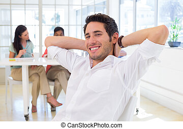 Businessman relaxing with coworkers in background in the...