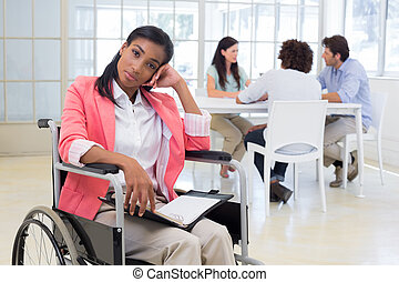 Woman with disability frowning with coworkers are in...