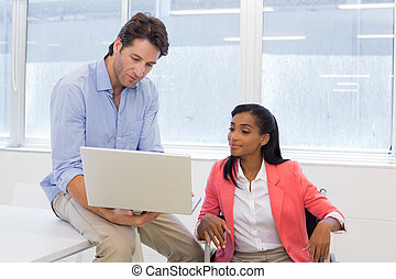Businessman showing woman in wheelchair document on laptop