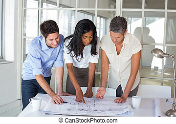 Three architects looking at blueprints