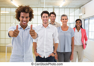 Group of business people giving thumbs up to camera in the...