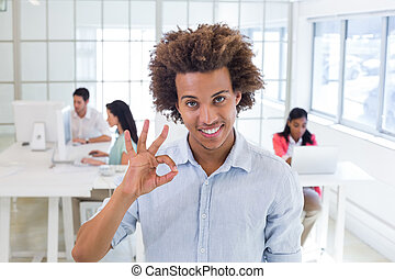 Businessman giving OK gesture to camera in the office