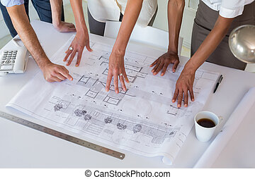 Architects looking at building plans carefully in the office