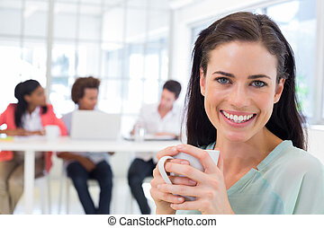Attractive businesswoman drinking coffee with coworkers in background in the office