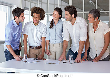 Casual business team having a meeting standing in the office
