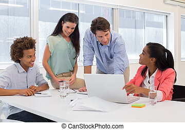Attractive business people working together on a laptop in...