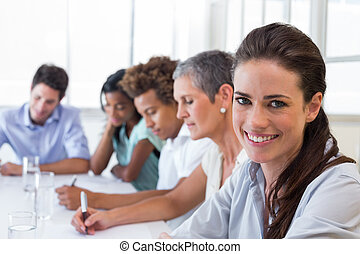 Businesswoman smiling at business meeting - Businesswoman...