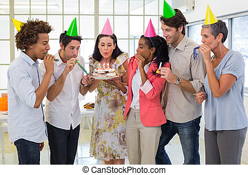Workers celebrating a birthday together in the office