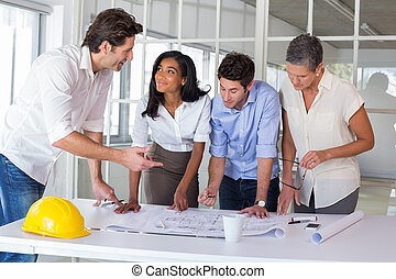 Team of architects going over blueprints in the office