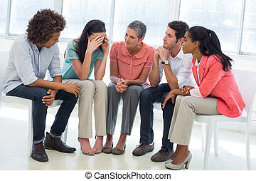 Group therapy in session sitting in a circle in a bright...