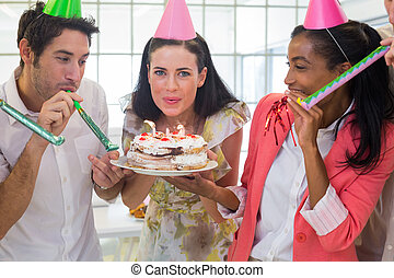 Businesswoman blowing out candles on cake in the office