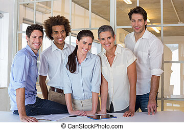 Casual group of coworker friends smiling at camera during...