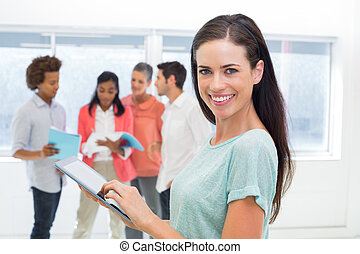 Attractive businesswoman using tablet with coworkers behind...
