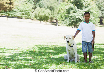 Little boy standing with his pet labrador in the park on a...