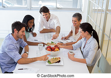 Business people eating sandwiches and fruit for lunch