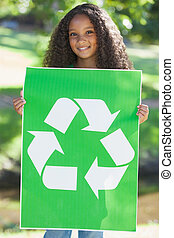 Young environmental activist smiling at the camera holding a poster on a sunny day
