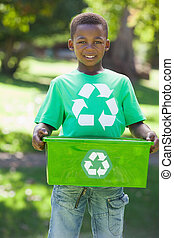 Young boy in recycling tshirt holding box on a sunny day