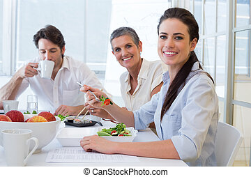 Workers eat lunch and drink coffee in the office