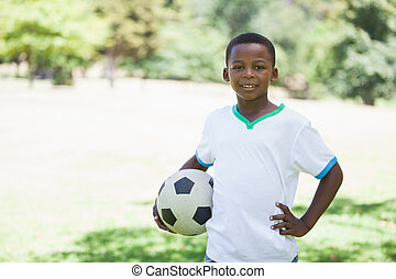 Little boy holding football in the park smiling at camera