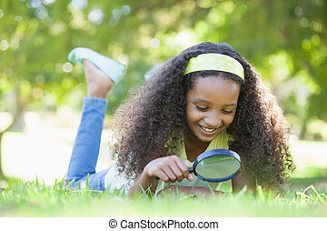 Young girl looking at grass through magnifying glass in the...