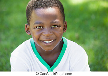 Cute boy smiling at the camera in the park on a sunny day