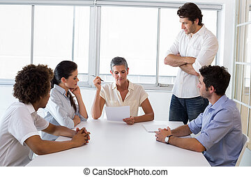 Serious businesswoman speaking to her coworkers - Attractive...