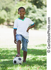 Little boy standing with football in the park on a sunny day