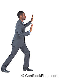 Businessman standing and pushing with hands on white...