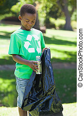 Young boy in recycling tshirt picking up trash on a sunny...
