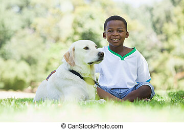Little boy sitting with his pet labrador in the park on a...