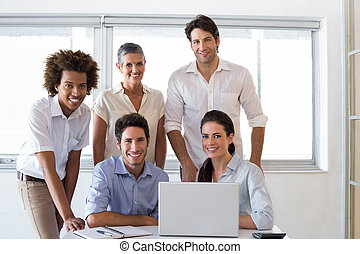 Attractive business people smiling at the camera whilst...