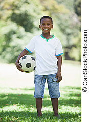Little boy holding football in the park smiling at camera on...