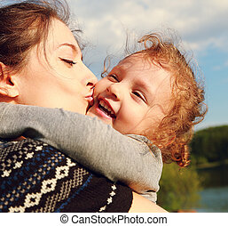 Mother kissing happy child outdoors summer background....