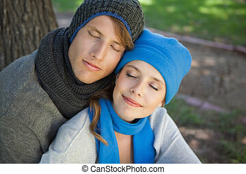 Cute couple sitting and embracing in the park with eyes closed