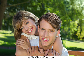Cute couple embracing in the park smiling at camera
