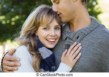 Cute woman smiling at camera with her boyfriend on a sunny...