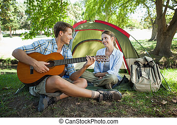 Cute man serenading his girlfriend on camping trip on a...